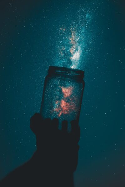 creative photo of person holding glass mason jar under a starry sky